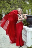 Fashion elegant blond woman model in red gown with blowing fabri Royalty Free Stock Images