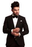 Fashion elegant man in tuxedo fixing his sleeve. On white background Royalty Free Stock Photo