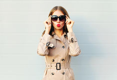 Fashion elegant pretty young woman blowing red lips wearing a black sunglasses coat over grey. Background Stock Photo