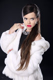 Fashion elegant woman in fur coat, Beautiful Brunette with red l Stock Images