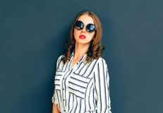 Fashion elegant woman lady wearing a black sunglasses posing. Over a gray background Stock Photo