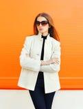 Fashion elegant woman wearing a white coat against orange. Background Stock Images