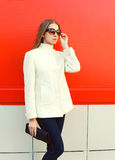Fashion elegant woman wearing a white coat jacket with clutch bag over red Royalty Free Stock Photography