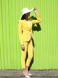 Fashion elegant woman wearing yellow suit clothes and straw haе Stock Image