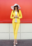 Fashion elegant woman wearing a yellow suit clothes, straw hat Royalty Free Stock Images