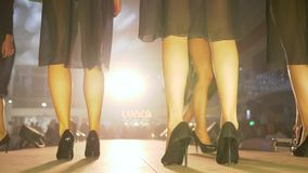 Fashion evening, slender legs of models in black high-heeled shoes walk on podium in bright light close-up on unfocused