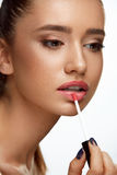 Fashion Female Model With Beauty Face Applying Lip Balm On Lips. Lip Makeup. Portrait Of Beautiful Sexy Woman With Perfect Smooth Skin Applying Lip Gloss On Royalty Free Stock Image