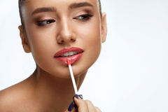 Fashion Female Model With Beauty Face Applying Lip Balm On Lips. Lip Makeup. Portrait Of Beautiful Sexy Woman With Perfect Smooth Skin Applying Lip Gloss On Stock Images