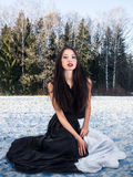 Fashion female in snow forest. Fashion girl sits on the snow in winter forest Royalty Free Stock Photo