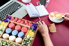 Fashion feminine pink home office workplace with laptop, box wit. H macaroons, smart phone and notebook royalty free stock photo
