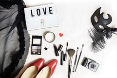 Fashion flat. Flat lay fashion female items. top view to holiday party preparation: red shoes, cloth, make up with brushes, photo camera, carnival mask, word Royalty Free Stock Photo