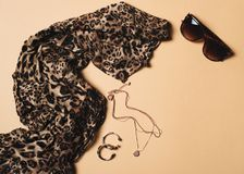 Fashion flat lay with leopard print scarf and accessories. On beige background, top view, copy space stock images