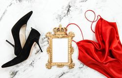 Fashion flat lay Red dress black high heels golden frame. Fashion flat lay. Red dress, black high heels, golden picture frame on marble background Royalty Free Stock Image