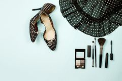 Fashion flat lay. Top view polka dot shoes with high heels and a skirt, make up kit with brushes Stock Photos