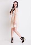 Fashion flickan i krämig klänning som poserar i studio Arkivbilder
