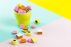Fashion food candy: liquorice allsorts in a yellow cup. Yellow, turquoise, pink Royalty Free Stock Photography