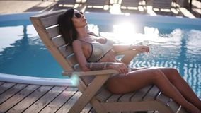 Fashion footage of beautiful tanned woman with brown hair in elegant silver bikini relaxing beside a swimming pool in. Sunglasses. Sun shines and flashing on a stock footage