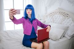 Fashion freak. Glamour emotionless synthetic girl, fake doll with blue hair is holding computer and doing selfie while. Sitting on the bed. Stylish beautiful royalty free stock image