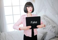 Fashion freak. Glamour synthetic girl, fake doll with empty look and short black hair is holding paper with word Fake. While standing near the bed. Stylish royalty free stock image