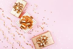 Fashion gift or present boxes with golden bows, serpentine and star confetti on pink pastel table top view. Christmas flat lay. Fashion gift or present boxes royalty free stock photos