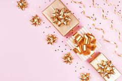 Fashion gift or present boxes with golden bows, serpentine and star confetti on pink pastel table top view. Christmas flat lay. Fashion gift or present boxes royalty free stock image