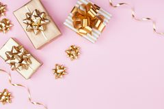 Fashion gifts or presents boxes with golden bows on pink pastel background top view. Flat lay for birthday or christmas. stock photos