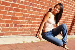 Fashion Girl. Fashionable young woman against red brick wall royalty free stock photos