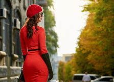 Fashion girl from back in red dress on the sun street Stock Photography