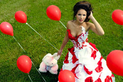 Fashion girl with baloons on grass bacground Royalty Free Stock Image
