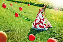 Fashion girl with baloons on grass bacground Royalty Free Stock Images