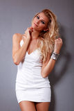 Fashion girl. Beautiful fashion female model in white dress is posing on gray background Royalty Free Stock Photos