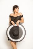 Fashion girl in a big hat in the studio stock images