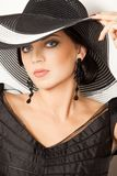 Fashion girl in a big hat in the studio royalty free stock photography
