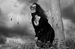 Fashion girl in black coat standing in grass near a wooden pole. Fashion happy girl in black coat standing in grass near a wooden pole and smiling Stock Photo
