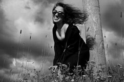 Fashion girl in black coat standing in grass near a wooden pole. Fashion happy girl in black coat standing in grass near a wooden pole and smiling Royalty Free Stock Photography