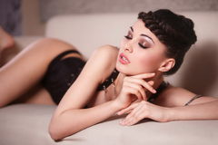 Fashion girl in black corset lying on the sofa Stock Photo