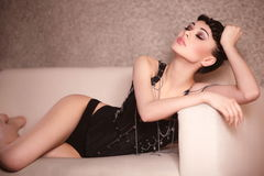 Fashion girl in black corset lying on the sofa Stock Photography