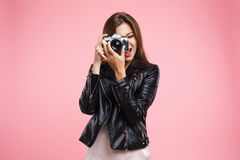 Fashion girl in black leather jacket holding old camera Royalty Free Stock Images