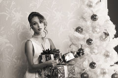 Fashion girl with christmas presents in BW. Black and white christmas portrait of stunning elegant fashion girl with some gift boxes near decorated xmas tree Royalty Free Stock Photography