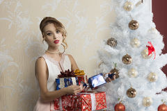 Fashion girl with christmas presents. Christmas portrait of stunning elegant fashion girl with some gift boxes near decorated xmas tree Stock Photos