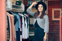 Fashion Girl in Clothing Store with Fedora Hat. Chic fashionable woman in a clothes shop looking for new garments Stock Images