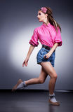 Fashion girl in denim shorts running in studio Royalty Free Stock Photography