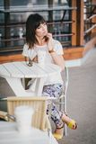 Fashion girl drinking coffee in a street cafe Royalty Free Stock Photography