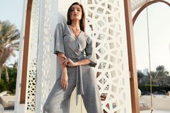 Fashion Girl. Fashionable Model In Fashion Clothes Posing. Outdoors. Beautiful Young Woman Wearing Stylish Trendy Grey Jumpsuit Relaxing At Luxury Resort In stock images