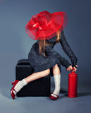 Fashion girl with fire extinguisher. In big red hat and red shoes Stock Images