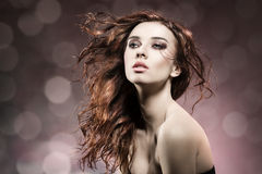 Fashion girl with flying hair on flare background Stock Image