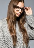 Fashion girl on a gray background in the studio posing with glasses royalty free stock images