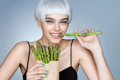 Fashion girl with green asparagus royalty free stock photo