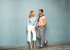 Fashion girl and guy in outlet clothes posing on a blue backgro. Und Royalty Free Stock Photo