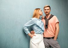 Fashion girl and guy in outlet clothes posing on a blue backgro. Und Stock Photos